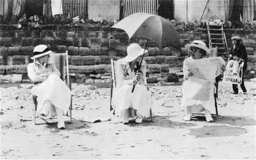 A newspaper seller whose board announces the declaration of war passes ladies on a beach somewhere on the South Coast.  A state of war existed between Great Britain and Germany as from 11 p.m. on Tuesday 4th August 1914.